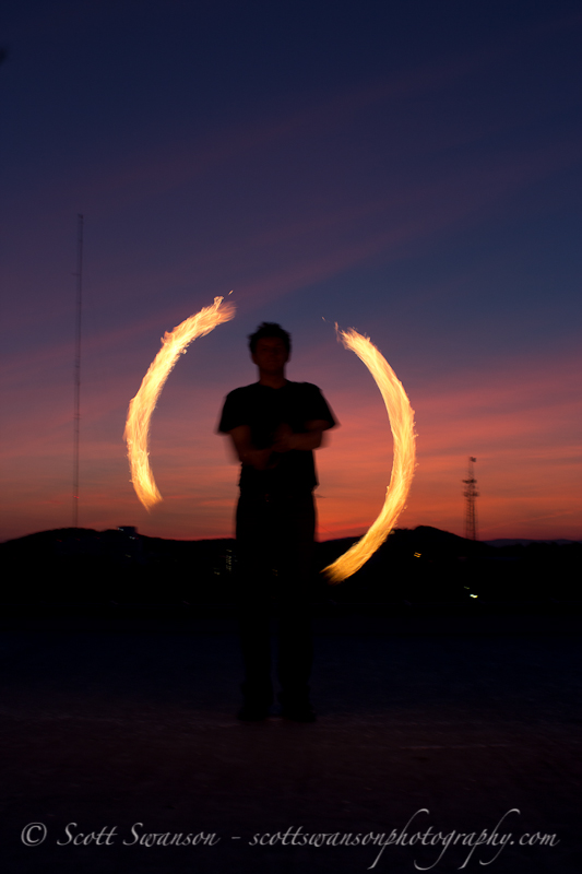 Shilouetted fire spinning against city backdrop