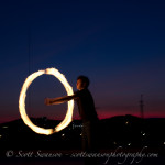 Fire spinning circle against a backdrop sunset over the city